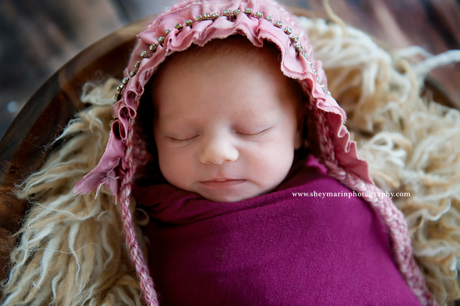 newborn girl in pink bonnet