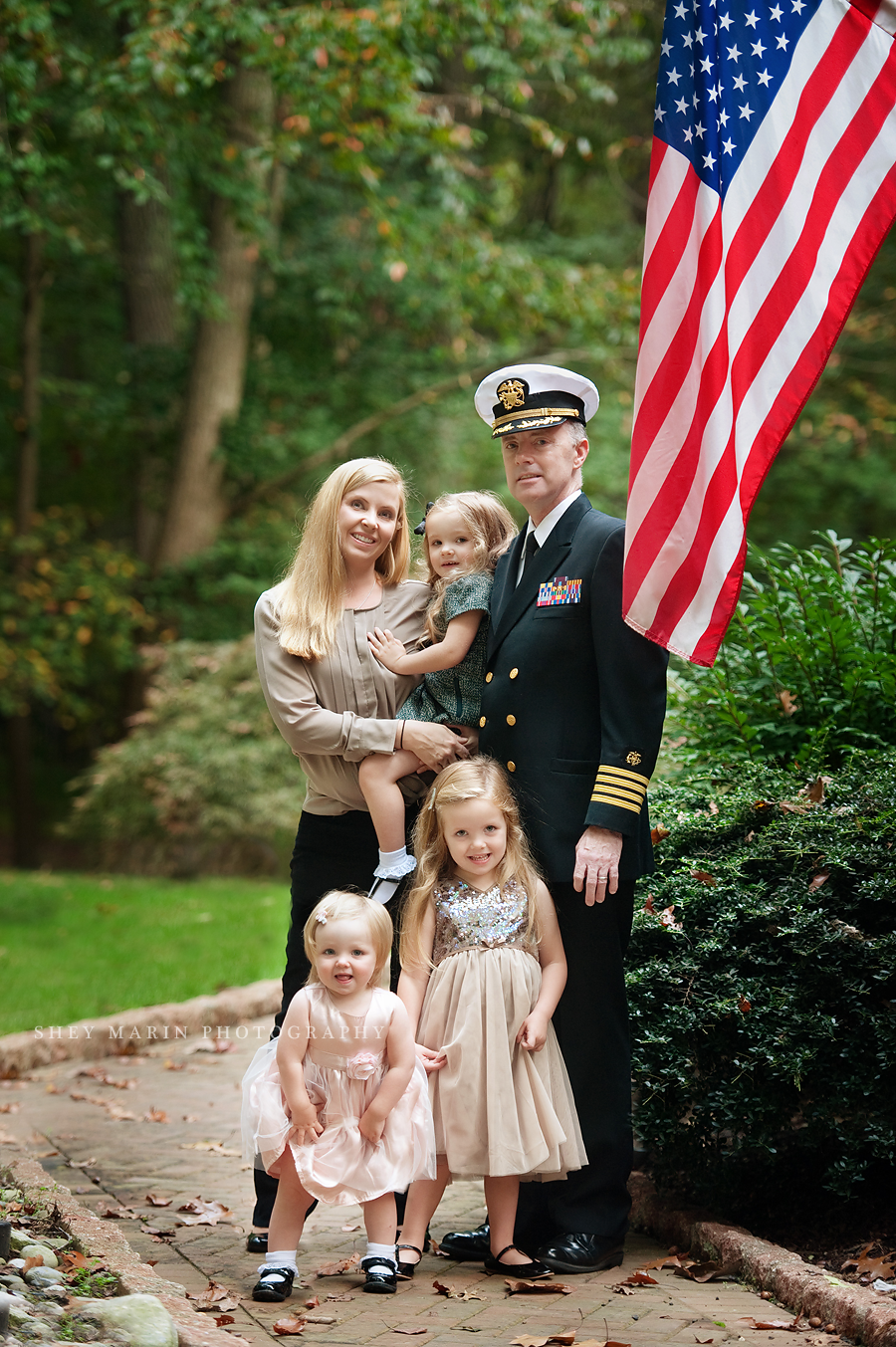 family in front of American flag with soldier father in uniform