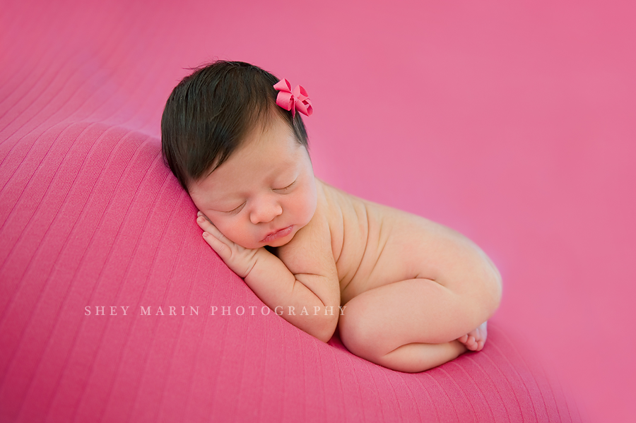 newborn baby girl on hot pink blanket