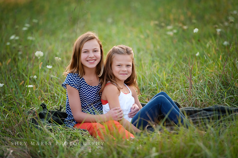 Two sisters smiling in the grass