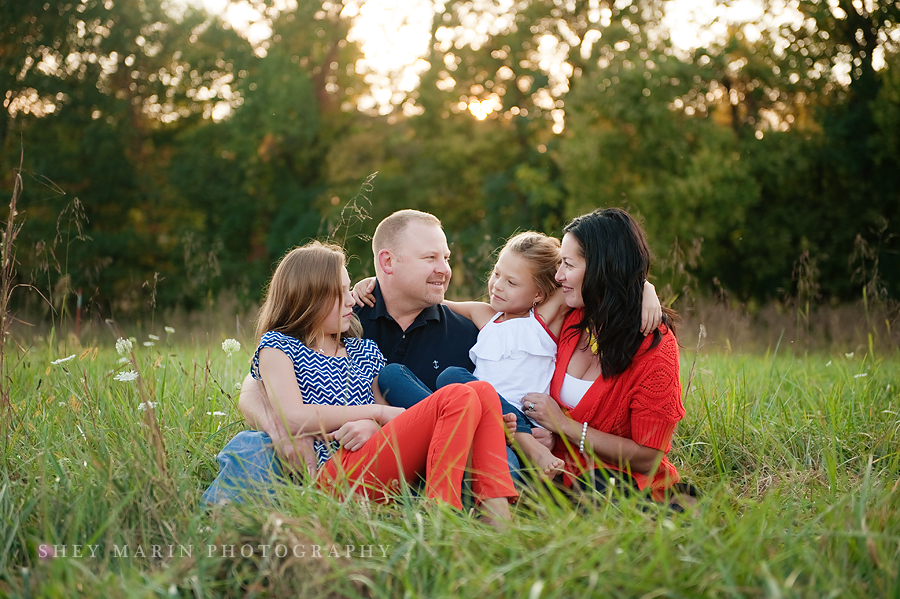 family laughing together in the tall grass