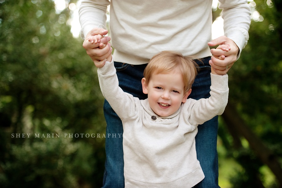 little boy holding his daddy's hands