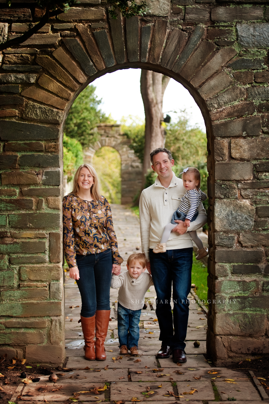 family standing in stone archway