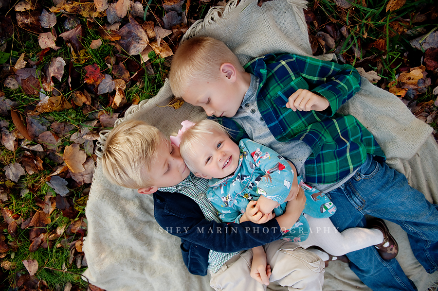 three kids laying in leaves