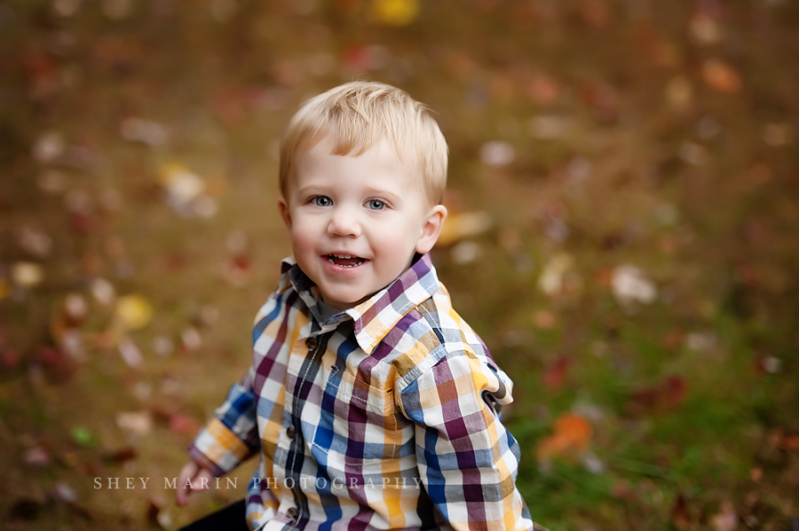 little boy smiling in fall leaves