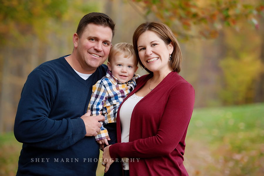 family smiling together in fall foliage