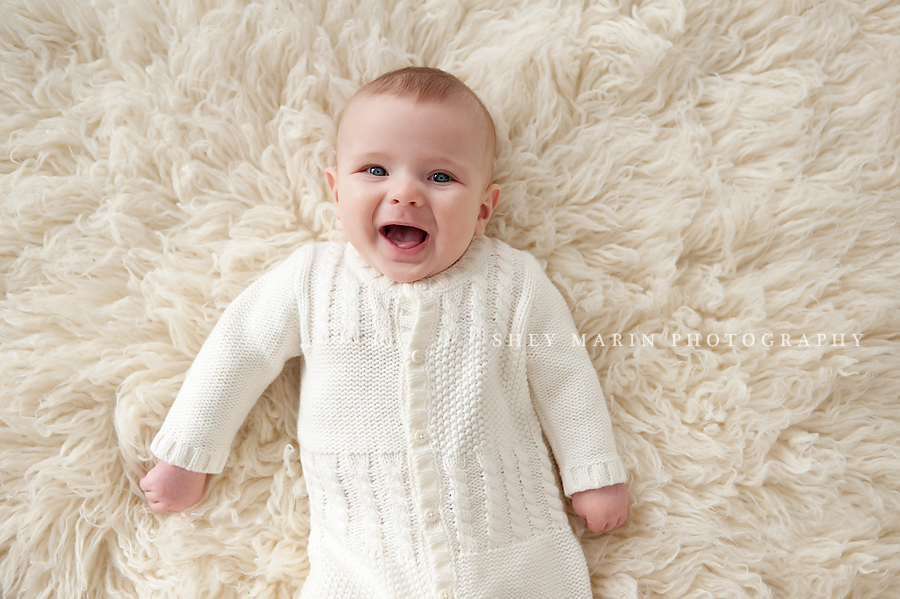 baby boy smiling on cream fur blanket