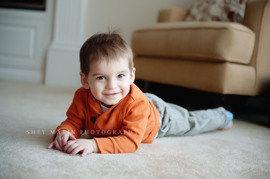 Toddler boy in orange smiling on floor