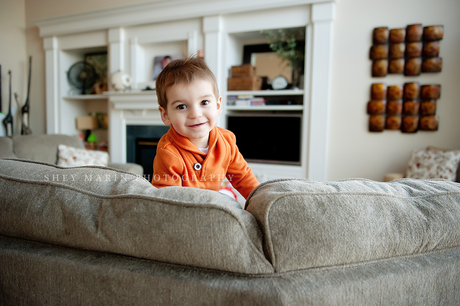Little boy peeking over a couch in Frederick, MD