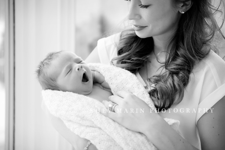 baby girl yawning in mother's arms