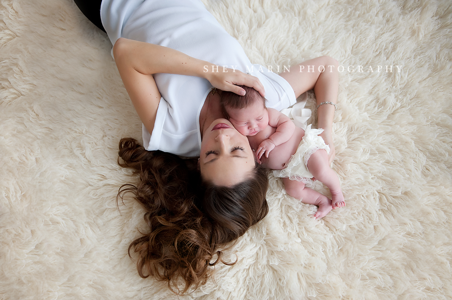 mother and newborn lying on floor with eyes closed