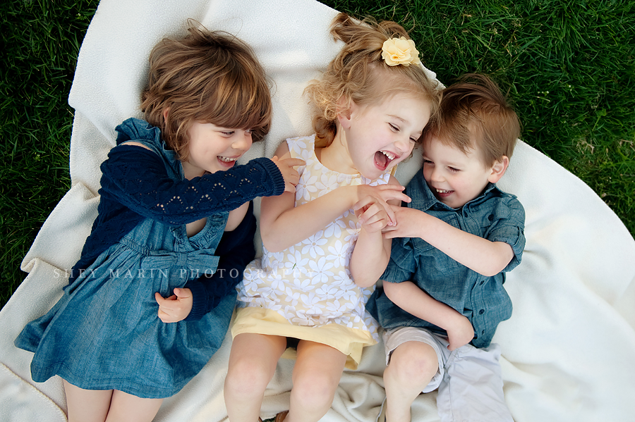 three toddlers laughing on a blanket in the grass