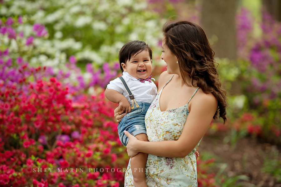 boy smiling in mom's arms with azaleas
