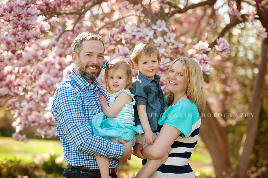 happy family smiling in cherry trees