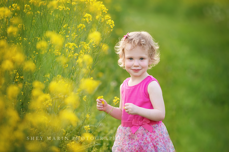 little girl in yellow wildflower field