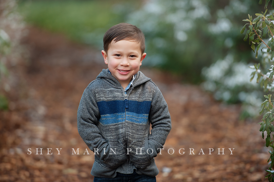 sweet boy in family playing in a winter garden