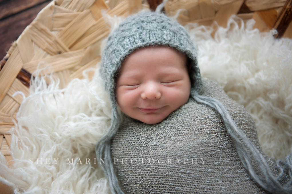 newborn baby boy in grey wrap in basket