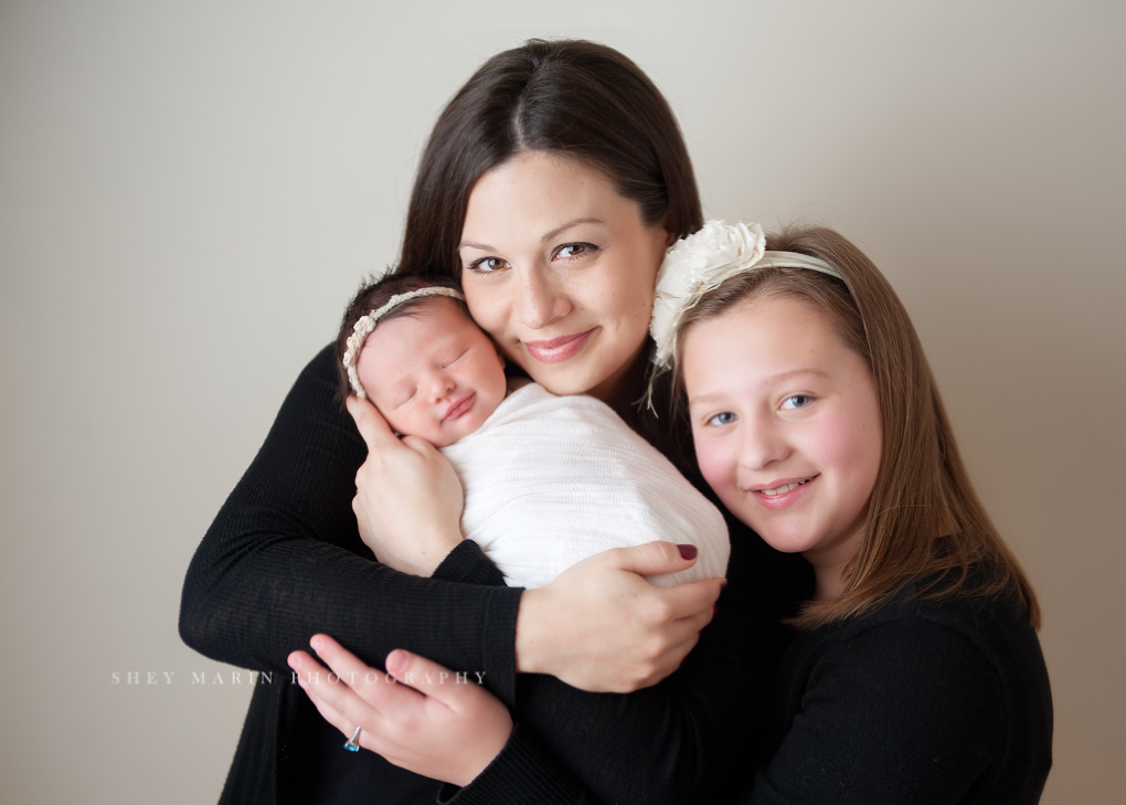 mom holding baby and older sister | Frederick Maryland newborn photographer