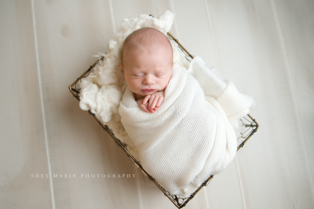 newborn boy in cream blanket