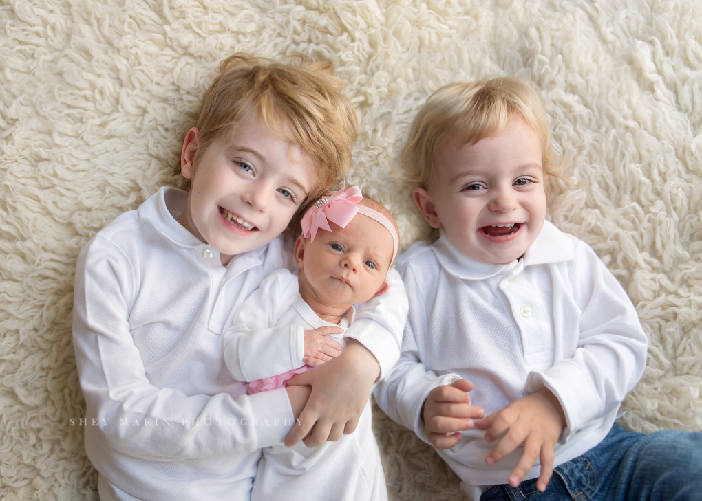 new baby girl photographed with big brothers